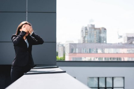Foto de Joven mujer de negocios, que sufre de miedo a las alturas, de pie en la azotea y cubriendo la cara con las manos - Imagen libre de derechos
