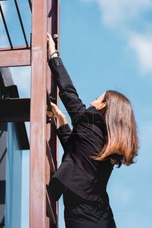 Photo for Young businesswoman in formal wear climbing stairs on rooftop - Royalty Free Image
