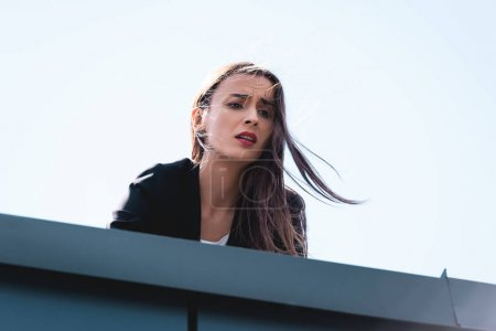 Photo for Young businesswoman, suffering from fear of heights, looking down rooftop - Royalty Free Image