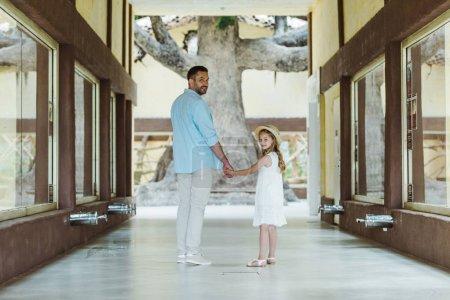 Foto de Padre feliz que se está torciendo de la mano con la hija alegre y linda en el sombrero de paja y vestido blanco mientras está de pie en el zoológico - Imagen libre de derechos