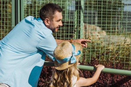 Photo pour Bel homme pointant avec le doigt à la cage tout en restant avec la fille dans le zoo - image libre de droit