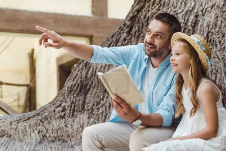 cheerful father holding book and pointing with finger near cute daughter in straw hat