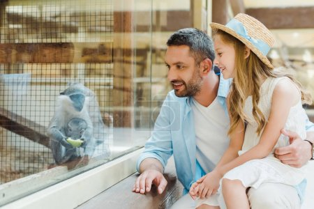 happy father and daughter looking at monkey while sitting near window in zoo