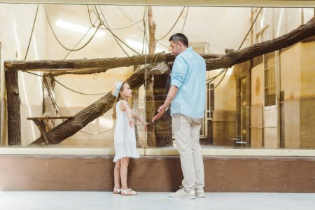 Photo for Cute daughter looking at father and showing shrug gesture in zoo - Royalty Free Image