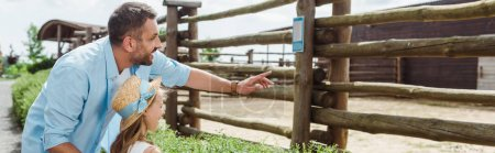 panoramic shot of happy man pointing with finger near daughter in straw hat while standing in zoo