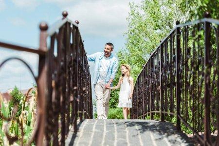 Photo pour Foyer sélectif du père retenant des mains avec la fille tout en marchant sur le pont - image libre de droit