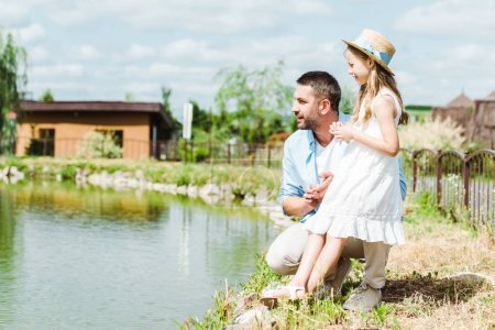 Photo for Cute kid in dress and straw hat standing near happy father and lake - Royalty Free Image