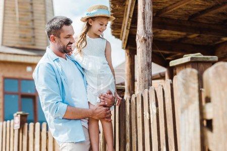 Foto de Enfoque selectivo de padre feliz sosteniendo en brazos linda hija cerca de la cerca de madera en el zoológico - Imagen libre de derechos