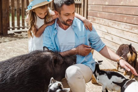 Photo for Cheerful man touching goat near cute daughter and boar in zoo - Royalty Free Image