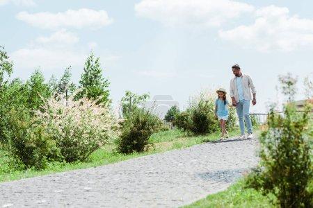 Photo pour Beau père et fille marchant près des plantes vertes et se tenant la main - image libre de droit