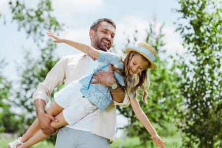 Photo pour Père gai retenant dans des bras descendant heureux dans le chapeau de paille - image libre de droit