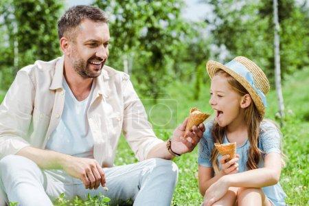 Photo pour Enfant gai avec bouche ouverte près du cône de crème glacée et père heureux - image libre de droit