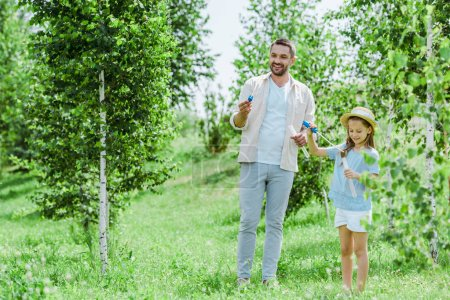 Photo for Selective focus of cheerful father and daughter holding bubble wands while standing near trees - Royalty Free Image