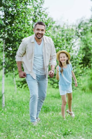 Photo for Cute and happy kid in straw hat gesturing near cheerful father looking at camera - Royalty Free Image