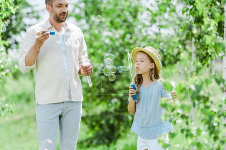Photo for Selective focus of cheerful father looking at daughter blowing soap bubbles - Royalty Free Image