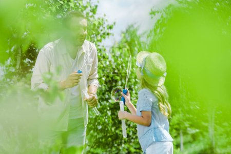 Photo for Selective focus of father and daughter in straw hat blowing soap bubbles near trees - Royalty Free Image