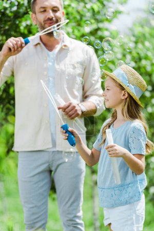 Photo pour Selective focus of cute daughter in straw hat holding bubble wand  near father blowing soap bubbles - image libre de droit
