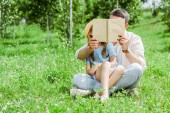 father and daughter covering faces while holding book and sitting on grass