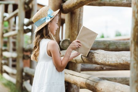 Photo for Selective focus of cute kid holding book near wooden fence - Royalty Free Image