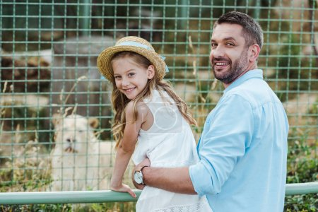 Photo pour Papa et descendant heureux regardant l'appareil-photo près de la cage avec l'animal sauvage dans le zoo - image libre de droit