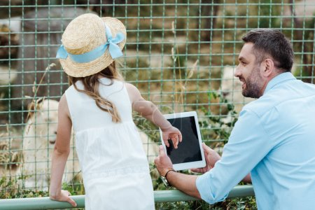 kid in straw hat gesturing near digital tablet with blank screen and father in zoo