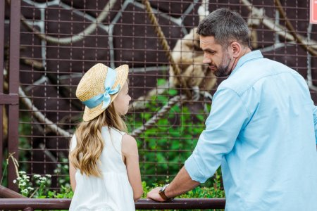 kid in straw hat looking at upset father near cage with wild animal in zoo