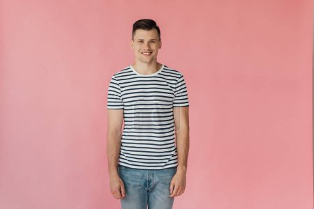 Photo pour Vue avant du jeune homme beau de sourire dans le t-shirt rayé regardant l'appareil-photo isolé sur le rose - image libre de droit
