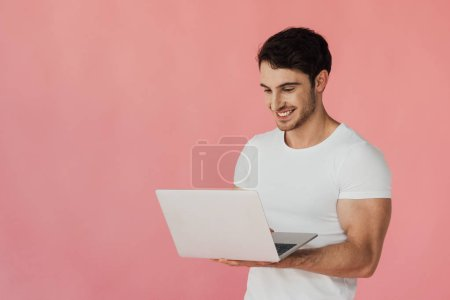 smiling muscular man in white t-shirt using laptop isolated on pink