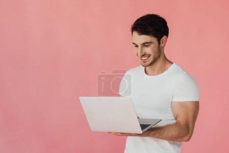 Photo pour Homme musclé souriant en t-shirt blanc en utilisant un ordinateur portable isolé sur rose - image libre de droit