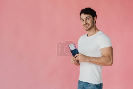 Photo pour Homme musclé souriant en t-shirt blanc tenant passeport et billet d'avion isolé sur rose - image libre de droit