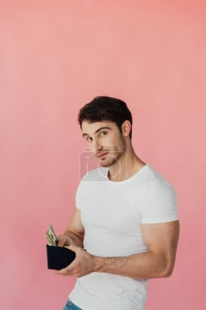 Photo for Muscular man in white t-shirt holding wallet with dollar banknotes and looking at camera isolated on pink - Royalty Free Image
