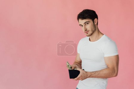 Photo pour Homme musculaire dans le portefeuille blanc de fixation de t-shirt avec des billets de banque de dollar et regardant l'appareil-photo isolé sur le rose - image libre de droit