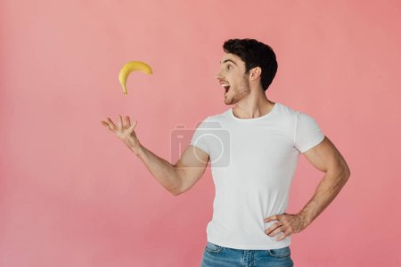 Photo for Smiling muscular man in white t-shirt throwing up banana isolated on pink - Royalty Free Image