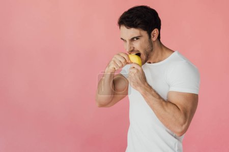 Photo for Hungry muscular man in white t-shirt eating banana isolated on pink - Royalty Free Image