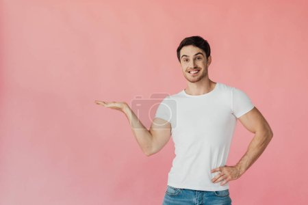 front view of excited muscular man in white t-shirt pointing with hand isolated on pink