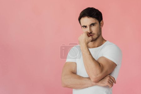 Photo for Serious pensive muscular man in white t-shirt looking at camera isolated on pink - Royalty Free Image
