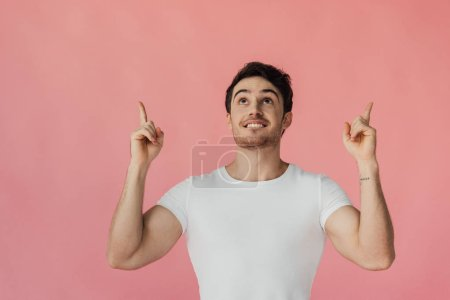 Photo for Front view of excited muscular man in white t-shirt pointing with fingers and looking up isolated on pink - Royalty Free Image