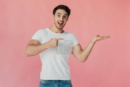 Photo for Excited muscular man in white t-shirt pointing with hand and pointing with finger isolated on pink - Royalty Free Image