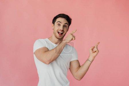 Foto de Hombre musculoso excitado en camiseta blanca apuntando con los dedos aislados en rosa - Imagen libre de derechos