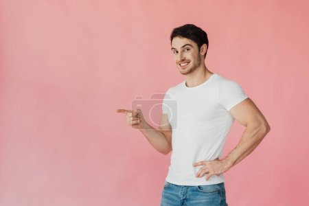 smiling muscular man in white t-shirt standing with hand on hip and pointing with finger isolated on pink