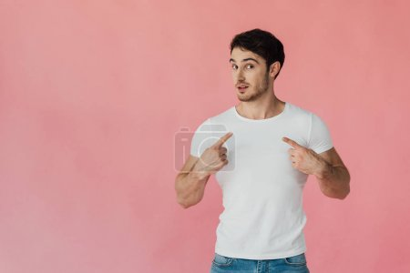 muscular man in white t-shirt pointing with fingers at himself isolated on pink