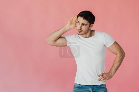 Photo for Muscular man in white t-shirt holding palm near ear and listening isolated on pink - Royalty Free Image