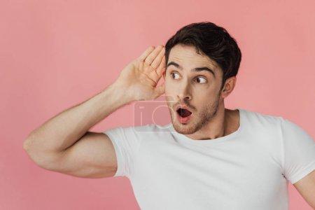 Photo pour Homme musculaire choqué dans le t-shirt blanc retenant la paume près de l'oreille et écoutant avec la bouche ouverte d'isolement sur le rose - image libre de droit