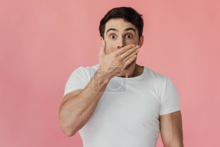 Photo for Front view of shocked muscular man in white t-shirt covering mouth with hand isolated on pink - Royalty Free Image