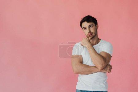 Photo pour Homme musculaire pensive dans le t-shirt blanc d'isolement sur le rose - image libre de droit