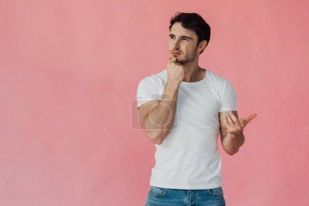 Photo pour Cher homme musclé en t-shirt blanc étançant visage avec poing et comptant sur les doigts isolés sur rose - image libre de droit