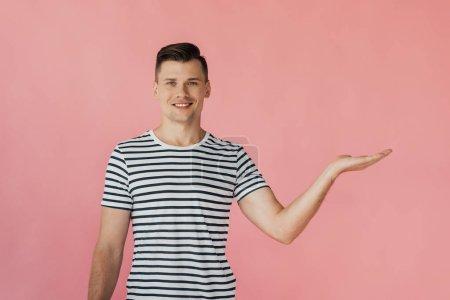 Photo pour Vue avant de l'homme de sourire dans le t-shirt rayé pointant avec la main d'isolement sur le rose - image libre de droit