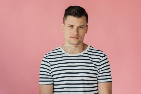 Photo for Front view of handsome man in striped t-shirt looking at camera isolated on pink - Royalty Free Image