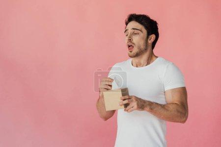 Photo pour Homme musclé en t-shirt blanc tenant des serviettes et éternuant isolé sur rose - image libre de droit
