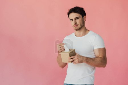 displeased muscular man in white t-shirt holding napkins and looking at camera isolated on pink